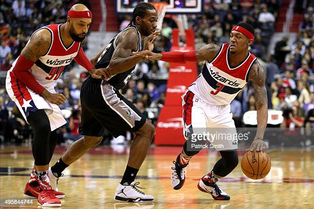Bradley Beal of the Washington Wizards dribbles in front of Kawhi Leonard of the San Antonio Spurs during the first half at Verizon Center on...
