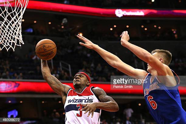 Bradley Beal of the Washington Wizards dunks in front of Kristaps Porzingis of the New York Knicks during the second half at Verizon Center on...