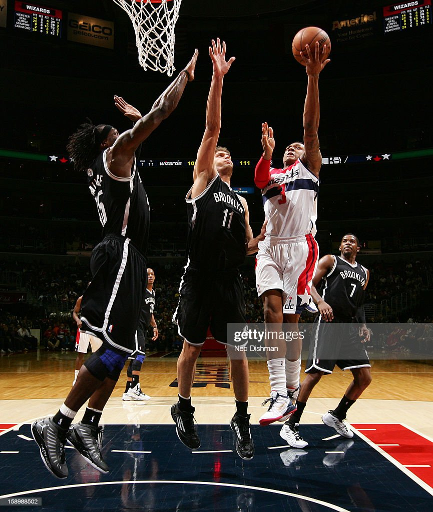 Bradley Beal #3 of the Washington Wizards shoots a layup against Brook Lopez #11 and Gerald Wallace #45 of the Brooklyn Nets during the game at the Verizon Center on January 4, 2013 in Washington, DC.