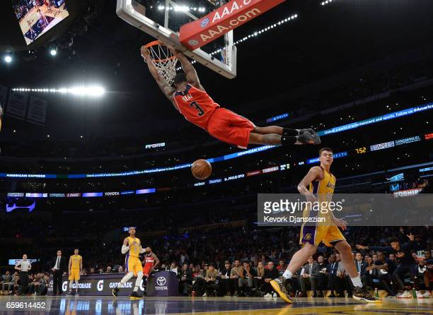 Bradley Beal of the Washington Wizards swings by the basket after a slam dunk against Ivica Zubac of the Los Angeles Lakers during the first half of...