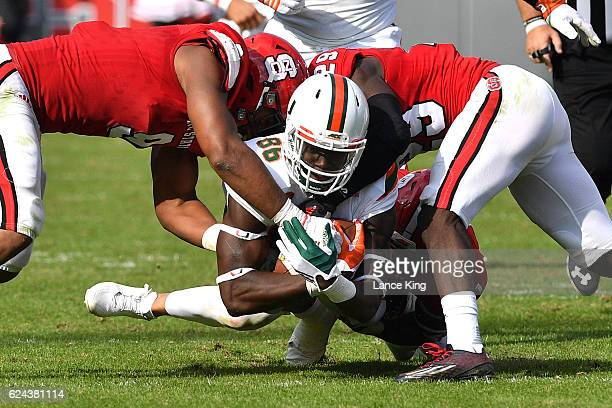 Bradley Chubb and Jack Tocho of the North Carolina State Wolfpack tackle David Njoku of the Miami Hurricanes at CarterFinley Stadium on November 19...