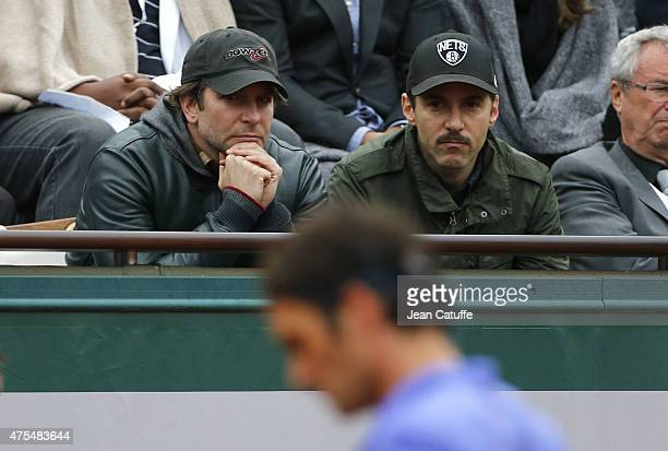 Bradley Cooper and Alessandro Nivola cheer for Roger Federer of Switzerland during his match on Center Court on day 8 of the French Open 2015 at...