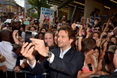 Bradley Cooper poses for a photo with fans at 'The Place Beyond The Pines' premiere during the 2012 Toronto International Film Festival at Princess...