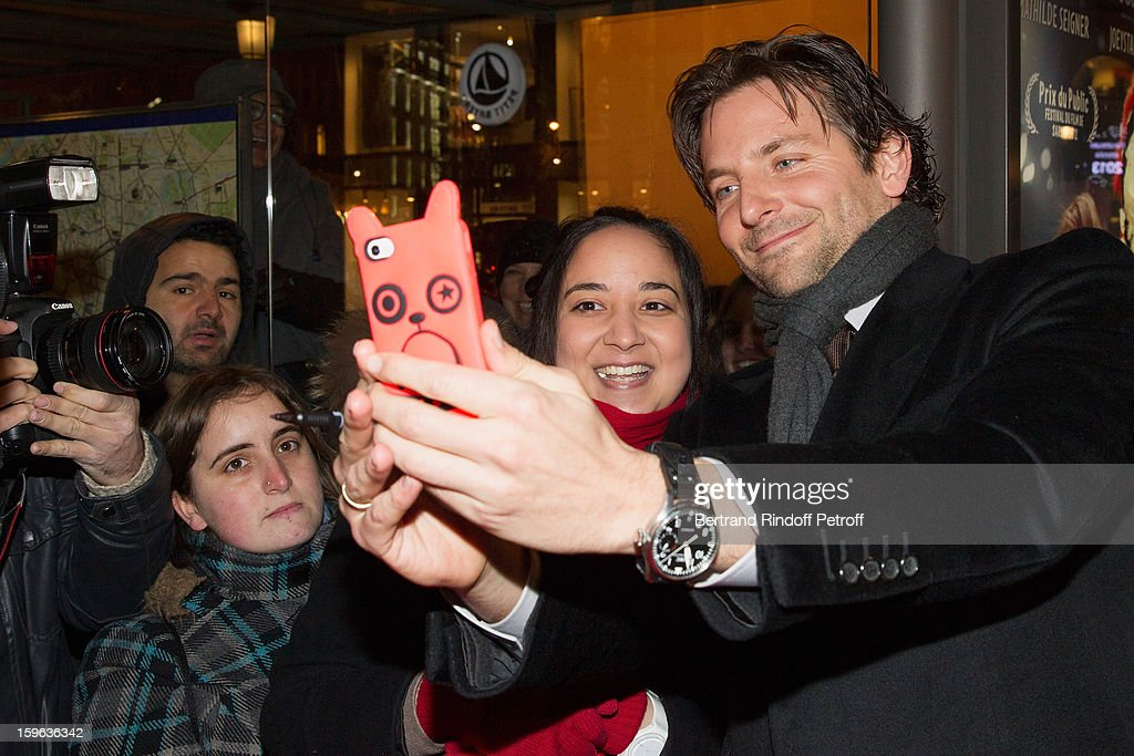 <a gi-track='captionPersonalityLinkClicked' href=/galleries/search?phrase=Bradley+Cooper&family=editorial&specificpeople=680224 ng-click='$event.stopPropagation()'>Bradley Cooper</a> (R) takes a photo of himself with a fan using a fan's mobile phone while arriving to the premiere of 'Happiness Therapy' (Silver Linings Playbook) at Cinema UGC Normandie on January 17, 2013 in Paris, France.