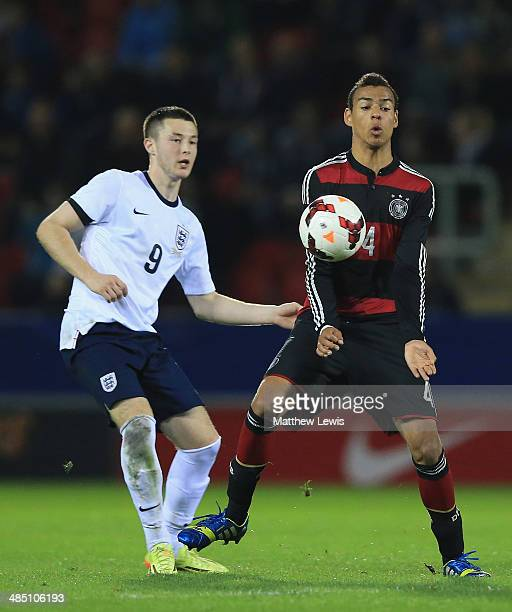 Bradley Fewster of England and Steffen Nkansah of Germany challenge for the ball during the Under 18 International Friendly match between England U18...