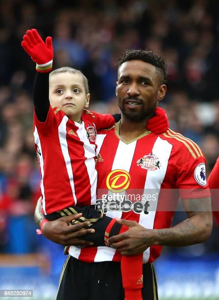 Bradley Lowery is held by Jermain Defoe of Sunderland as the teams line up prior to the Premier League match between Everton and Sunderland at...
