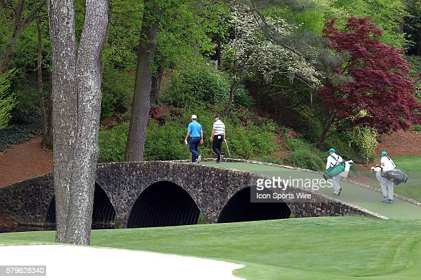 Bradley Neil and Rory McIlroy cross the Hogan Bridge during the practice round for the 2015 Masters Tournament at the Augusta National Golf Club in...