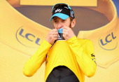 Bradley Wiggins of Great Britain and SKY Procycling kisses the maillot jaune as he celebrates on the podium after securing the yellow jersey of the...