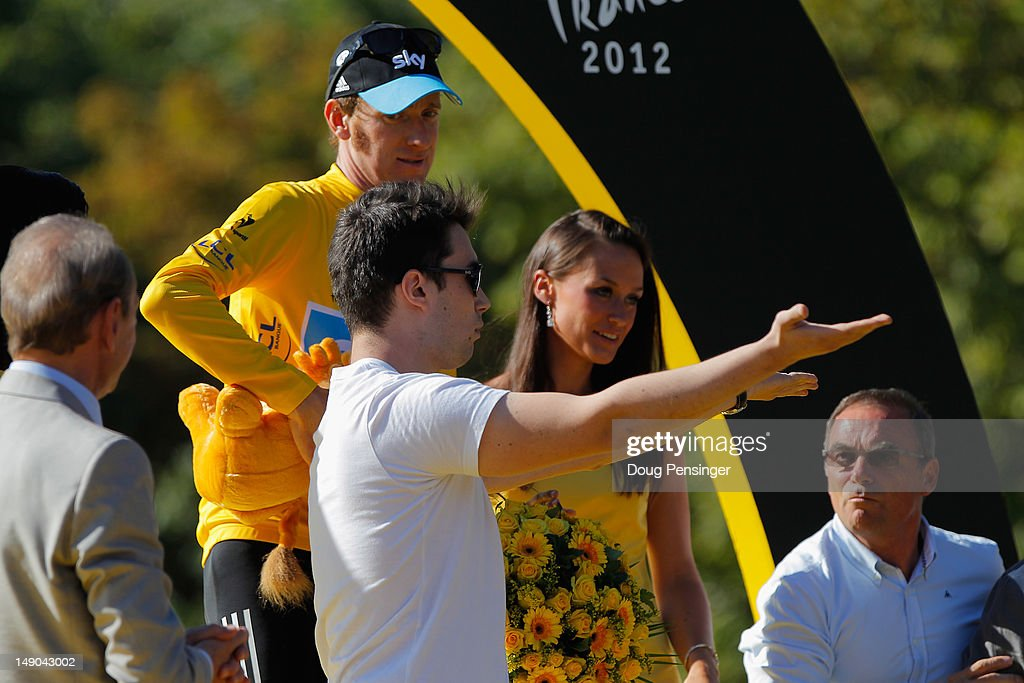 <a gi-track='captionPersonalityLinkClicked' href=/galleries/search?phrase=Bradley+Wiggins&family=editorial&specificpeople=182490 ng-click='$event.stopPropagation()'>Bradley Wiggins</a> of Great Britain and SKY Procycling looks on after receiving the maillot jaune as a podium invader takes to the stage after the twentieth and final stage of the 2012 Tour de France, from Rambouillet to the Champs-Elysees on July 22, 2012 in Paris, France.