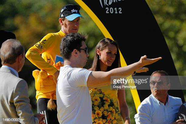Bradley Wiggins of Great Britain and SKY Procycling looks on after receiving the maillot jaune as a podium invader takes to the stage after the...