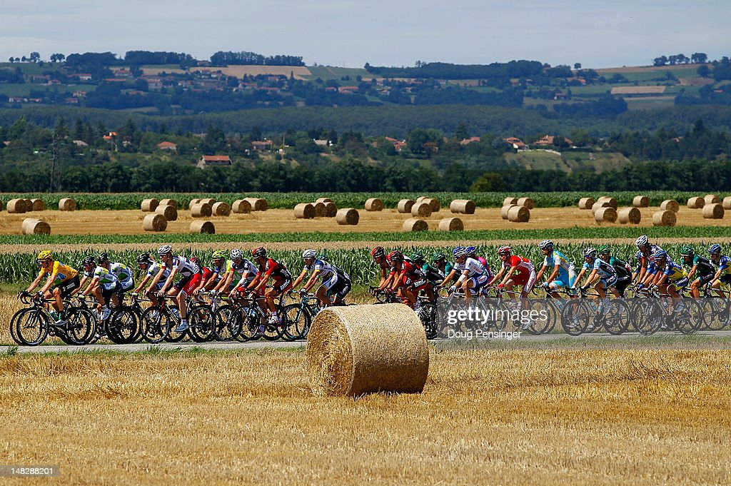 <a gi-track='captionPersonalityLinkClicked' href=/galleries/search?phrase=Bradley+Wiggins&family=editorial&specificpeople=182490 ng-click='$event.stopPropagation()'>Bradley Wiggins</a> (L) of Great Britain riding for Sky Procycling in the race leader's yellow jersey rides in the peloton as they pass through agricultural fields in stage twelve of the 2012 Tour de France from Saint-Jean de Maurienne to Annonay on July 13, 2012 in Anneyron, France.