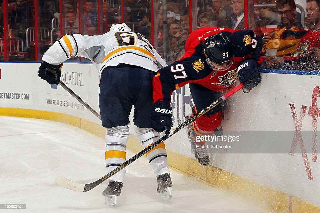 Brady Austin #67 of the Buffalo Sabres checks Matt Gilroy #97 of the Florida Panthers into the boards at the BB&T Center on October 25, 2013 in Sunrise, Florida.