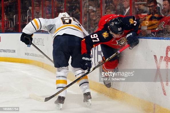 Brady Austin of the Buffalo Sabres checks Matt Gilroy of the Florida Panthers into the boards at the BBT Center on October 25 2013 in Sunrise Florida