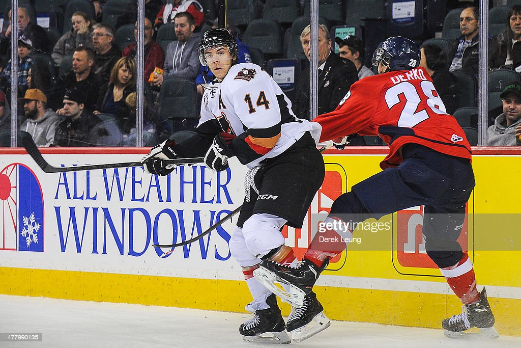 Brady Brassart #14 of the Calgary Hitmen gets shoved by Josh Derko #28 of the Lethbridge Hurricanes during a WHL game at Scotiabank Saddledome on March 11, 2014 in Calgary, Alberta, Canada.