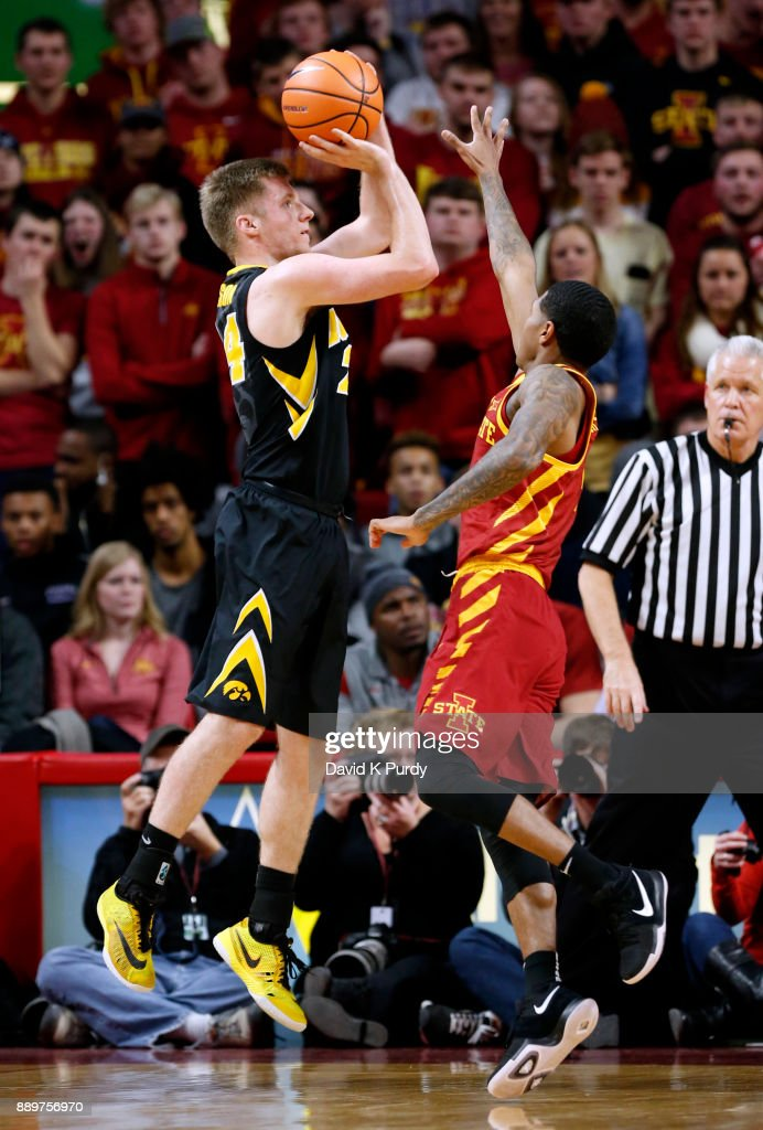 Brady Ellingson #24 of the Iowa Hawkeyes takes a shot as Donovan Jackson #4 of the Iowa State Cyclones blocks in the first half of play at Hilton Coliseum on December 7, 2017 in Ames, Iowa.