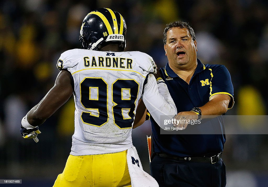 <a gi-track='captionPersonalityLinkClicked' href=/galleries/search?phrase=Brady+Hoke&family=editorial&specificpeople=3821056 ng-click='$event.stopPropagation()'>Brady Hoke</a>, coach of the Michigan Wolverines, congratulates <a gi-track='captionPersonalityLinkClicked' href=/galleries/search?phrase=Devin+Gardner&family=editorial&specificpeople=6427914 ng-click='$event.stopPropagation()'>Devin Gardner</a> #98 after a touchdown in the second half against the Connecticut Huskies at Rentschler Field on September 21, 2013 in East Hartford, Connecticut.