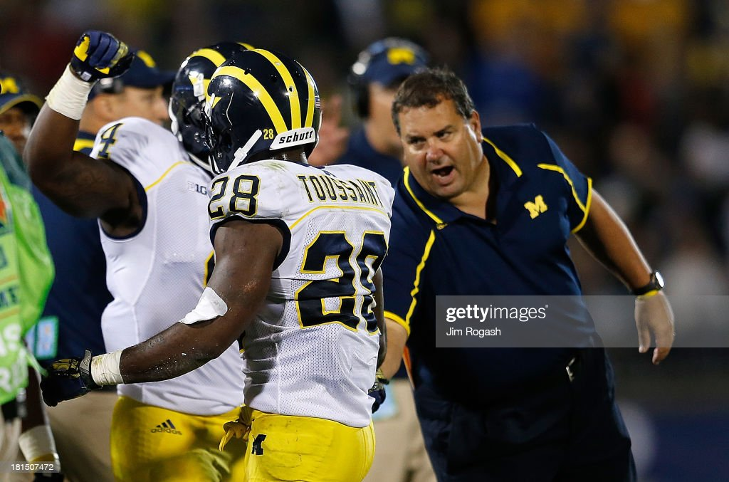 Brady Hoke, coach of the Michigan Wolverines, congratulates Fitzgerald Toussaint #28 of the Michigan Wolverines after the first of two touchdowns in the second half against the Connecticut Huskies at Rentschler Field on September 21, 2013 in East Hartford, Connecticut.