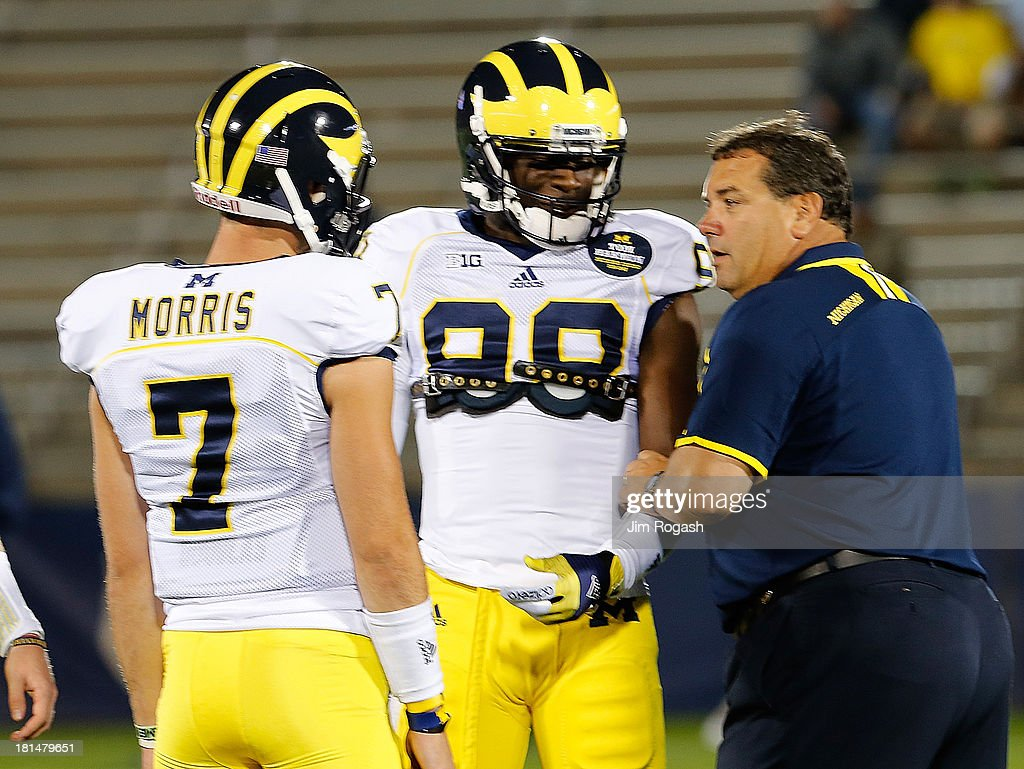 Brady Hoke, coach of the Michigan Wolverines, talks with Devin Gardner #98 and Shane Morris #7 before a game with the Connecticut Huskies at Rentschler Field on September 21, 2013 in East Hartford, Connecticut.