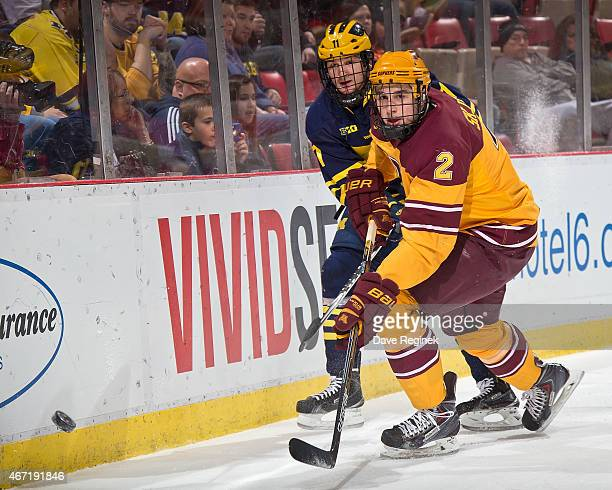 Brady Skjei of the Minnesota Golden Gophers clears the puck in front of Zach Hyman of the Michigan Wolverines during the finals of Big Ten Mens Ice...