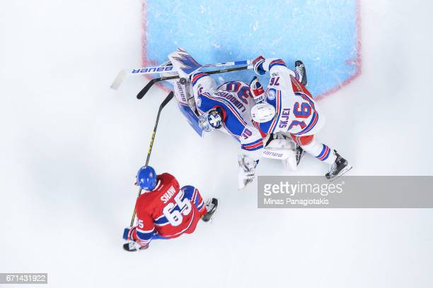Brady Skjei of the New York Rangers comes to the aid of goaltender Henrik Lundqvist as he makes a save on Andrew Shaw of the Montreal Canadiens in...
