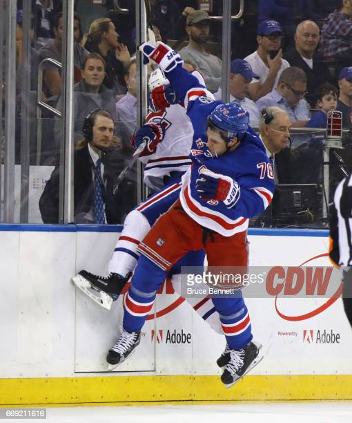 Brady Skjei of the New York Rangers hits Artturi Lehkonen of the Montreal Canadiens into the boards during the first period in Game Three of the...