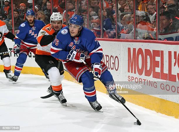 Brady Skjei of the New York Rangers skates the puck against Scott Laughton of the Philadelphia Flyers on November 25 2016 at the Wells Fargo Center...