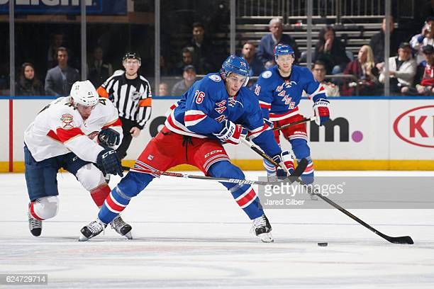Brady Skjei of the New York Rangers skates with the puck against Greg McKegg of the Florida Panthers at Madison Square Garden on November 20 2016 in...