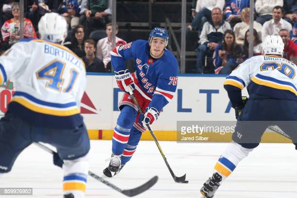 Brady Skjei of the New York Rangers skates with the puck against Robert Bortuzzo and Kyle Brodziak of the St Louis Blues at Madison Square Garden on...