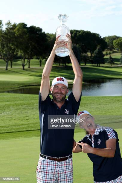 Brady Stockton the caddie of Cristie Kerr of the United States Team holds the Solheim Cup high above her after the closing ceremony during the final...