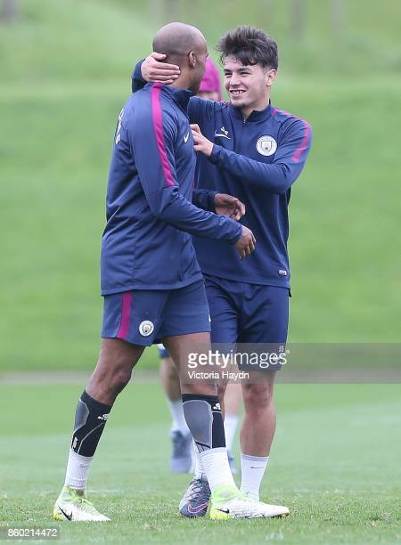 Brahim Diaz jokes with Fabian Delph during training at Manchester City Football Academy on October 11 2017 in Manchester England