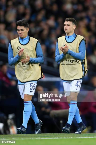 Brahim Diaz of Manchester City and teammate Phil Foden warm up on the sideline during the UEFA Champions League match between Manchester City v...