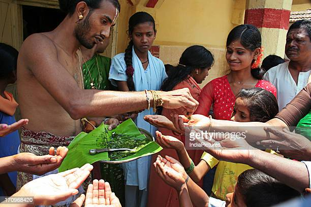 A Brahmin priest distributing a mixture of BevuBella to devotees during the Yugadi Festival which is the New Year's Day for people of the Deccan...