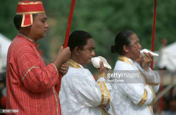 Brahmin priests dressed in white blow into conch shells as they lead the procession during the royal ploughing ceremony at the Royal Field The...