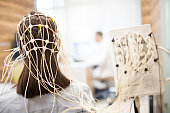 Rear view of girl with eeg electrode equipment on her head having medical test