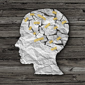 Brain disease therapy and mental health treatment concept as a sheet of torn crumpled white paper taped together shaped as a side profile of a human face on wood as a symbol for neurology surgery and