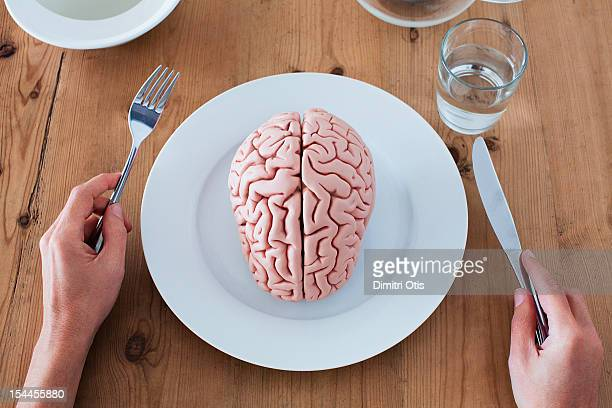 Brain on plate, hands holding cutlery