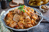Braised cabbage with turkey thigh meat on a wooden table, horizontal