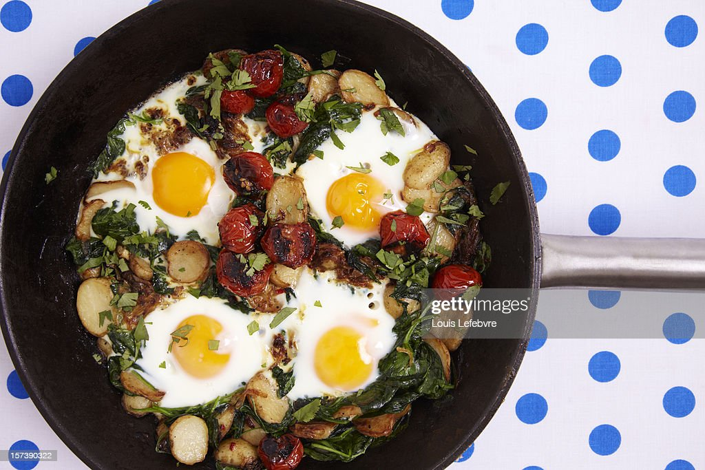 Braised eggs with tomato, spinach and yoghurt : Stock Photo