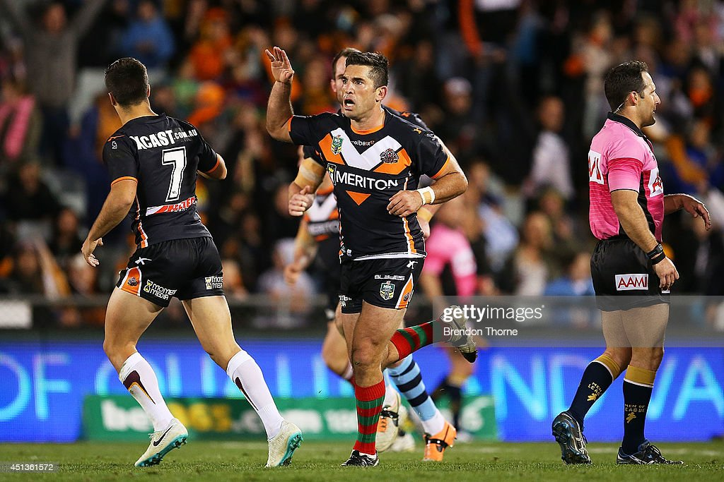 Braith Anasta of the Tigers celebrates with team mate Luke Brooks after kicking a field goal during the round 16 NRL match between the Wests Tigers and the Canberra Raiders at Campbelltown Sports Stadium on June 28, 2014 in Sydney, Australia.