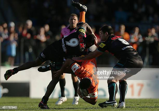 Braith Anasta of the Tigers is tackled by James Segeyaro of the Panthers during the round 17 NRL match between the Wests Tigers and the Penrith...
