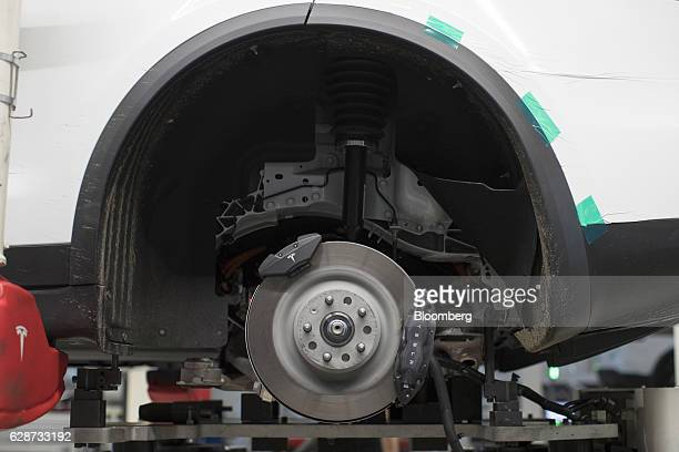 A brake disc sits on the rear axle of a Tesla Model X sports utility vehicle during assembly for the European market at the Tesla Motors Inc factory...