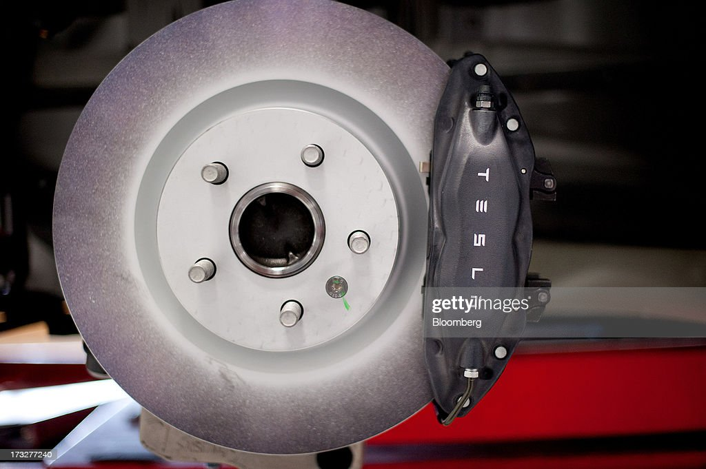 Brakes and a rotor are displayed on a Telsa Motor Inc. Model S sedan at the company's assembly plant in Fremont, California, U.S., on Wednesday, July 10, 2013. Tesla, is building Model S electric sedans faster than its initial 400-a-week goal as demand and the companys production skills increase, Chief Executive Officer Elon Musk said. Photographer: Noah Berger/Bloomberg via Getty Images