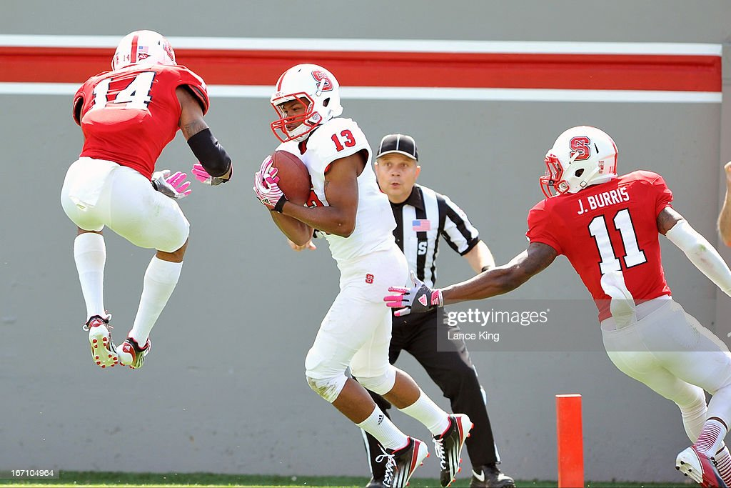 Bra'Lon Cherry #13 catches for a touchdown against Jarvis Byrd #14 and Juston Burris #11 of the North Carolina State Wolfpack during the Kay Yow Spring Football Game at Carter-Finley Stadium on April 20, 2013 in Raleigh, North Carolina.