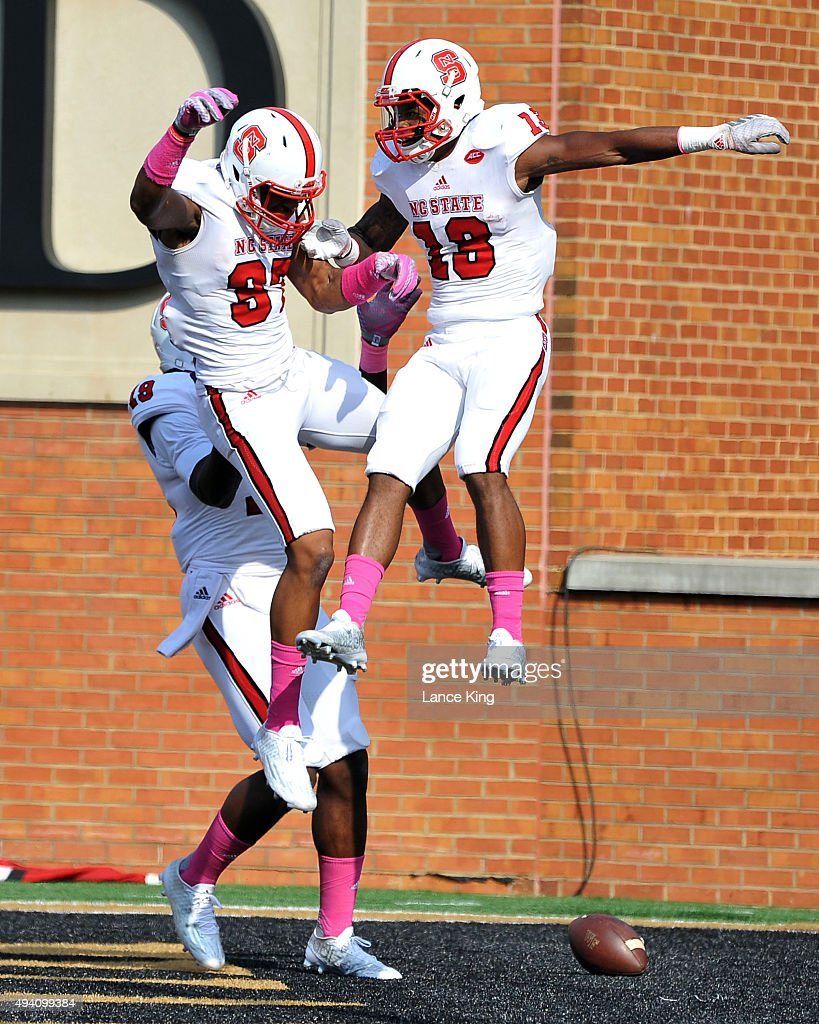 Bra'Lon Cherry of the North Carolina State Wolfpack celebrates his 52yard punt return touchdown with teammates Maurice Morgan and Josh Sessoms during...