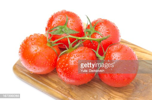branch of fresh tomatoes on wooden board isolated : Stockfoto