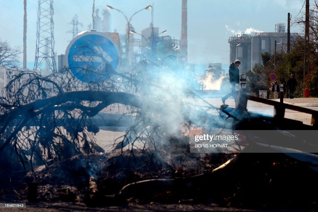Branches and crate burn as employees of Kem One, a French company specialized in chlorochemicals and vinyl products, block the access to their company in Lavera, southern France, on March 25, 2013 after French unions announced the company's cessation of payments. 350 jobs could be cut on the Lavera site. AFP PHOTO / BORIS HORVAT