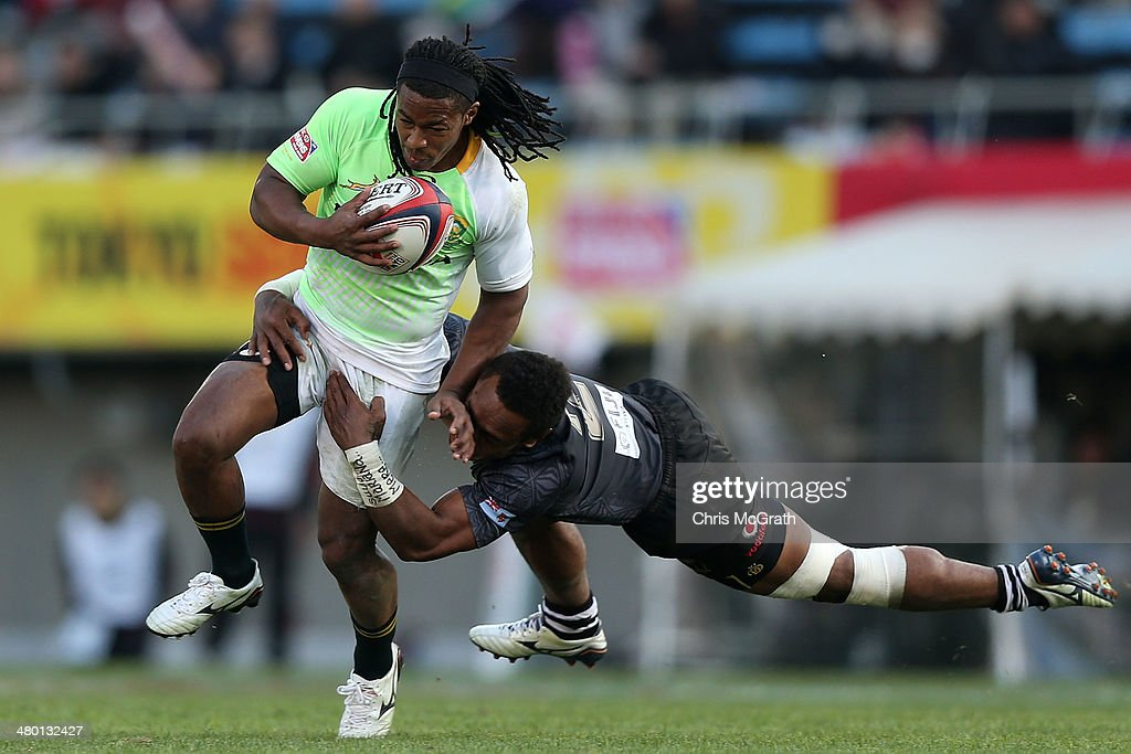 Branco du Preez #7 of South Africa is tackled by Benito Masilevu #2 of Fiji during the Cup Final at the Tokyo Sevens, in the six round of the HSBC Sevens World Series at the Prince Chichibu Memorial Ground on March 23, 2014 in Tokyo, Japan.
