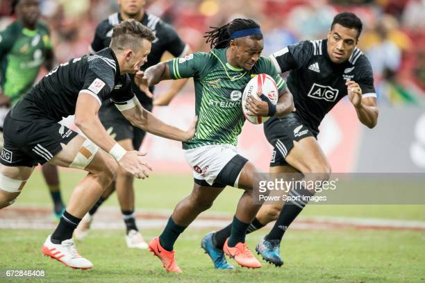 Branco Du Preez of South Africa runs with the ball while New Zealand players including Lewis Ormond try to stop him during the match South Africa vs...