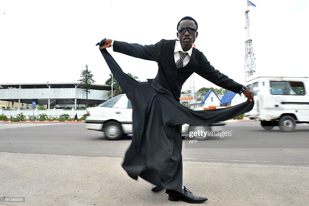 A brand fashion addict ('Sapeurs' in French) from Kinshasa arrives to take part in a tribute to Stervos Niarcos, on Feburary 10, 2013 on the 18th anniversary of Niarcos' death at the Gombe cemetery in Kinshasa. Niarcos was known as the leader of the 'Sape' movement and the founder of the 'Kitendi' religion, which means clothing in local Lingala language.