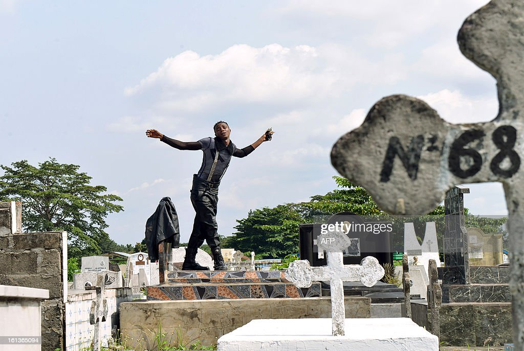 A brand fashion addict ('Sapeurs' in French) from Kinshasa dances on a grave as he takes part in a tribute to Stervos Niarcos, on Feburary 10, 2013 on the 18th anniversary of Niarcos' death at the Gombe cemetery in Kinshasa. Niarcos was known as the leader of the 'Sape' movement and the founder of the 'Kitendi' religion, which means clothing in local Lingala language.